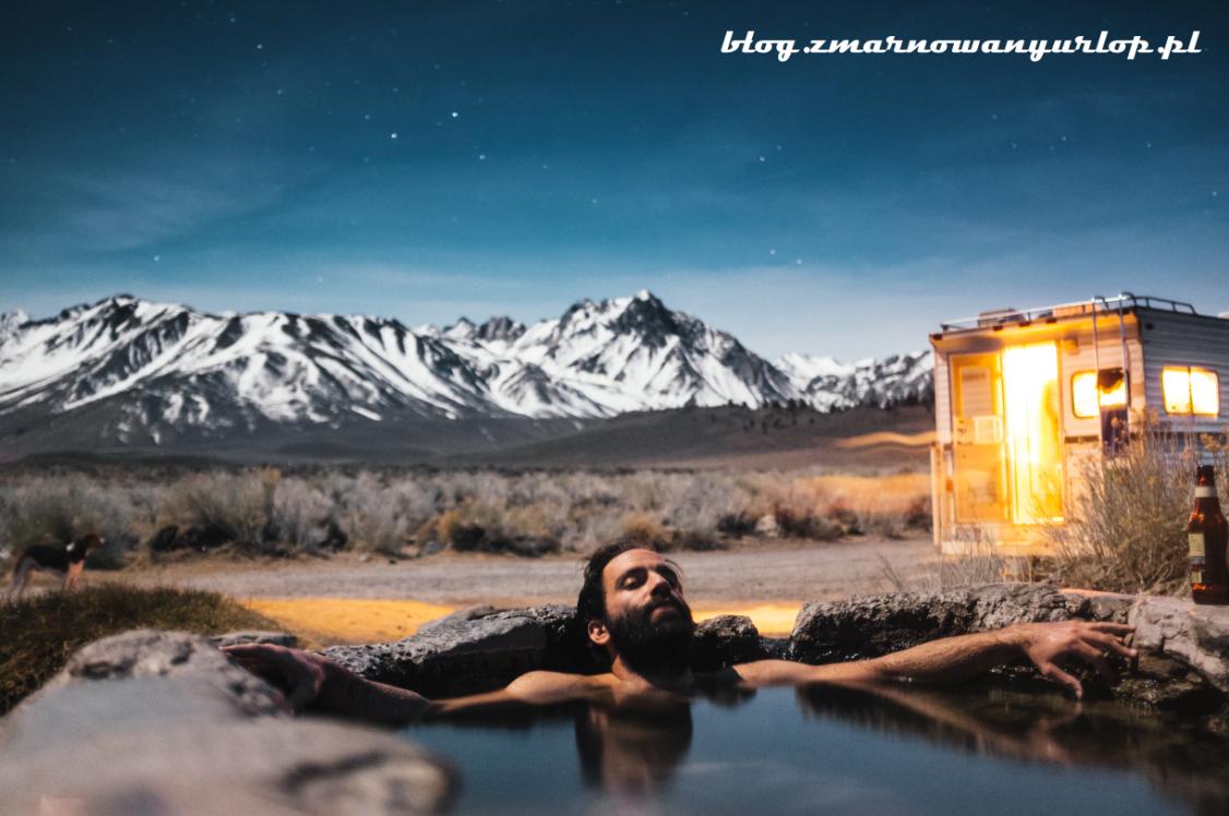 mężczyzna relaksujący się w źródełku na tle gór ilustracja do tekstu wakacje z biurem podróży